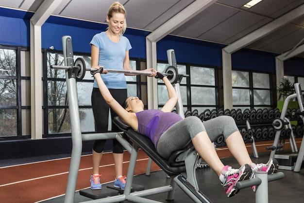 ジムでバーベルを持ち上げる妊娠中の女性を助ける笑顔のトレーナー
