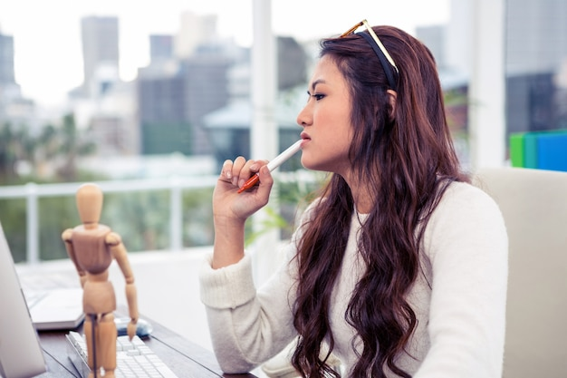 アジアの女性のオフィスであごにペンで集中