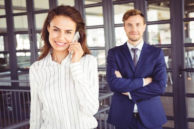 Портрет бизнесмена и бизнесвумен, улыбаясь в офисе