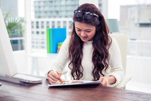 アジアの女性の笑顔のオフィスで書類を見て