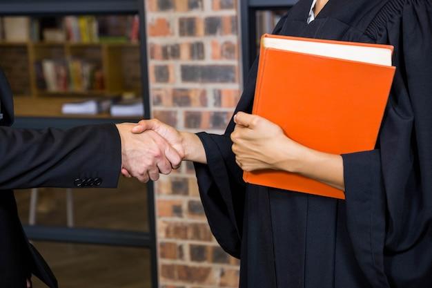 オフィスの弁護士と握手するビジネスマン