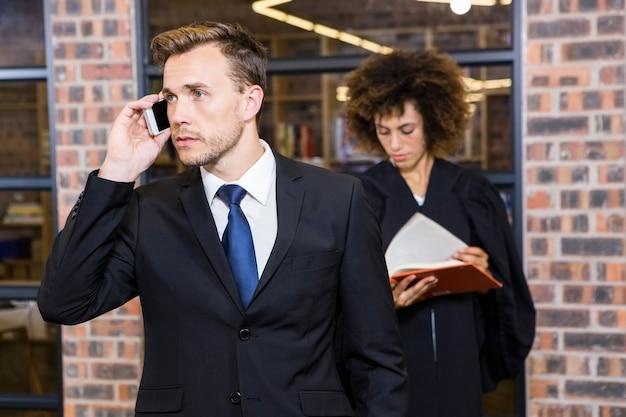 Бизнесмен, говорить на смартфоне и юрист, читая книгу законов