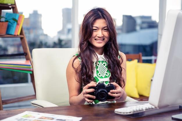 アジアの女性のオフィスでカメラを持って笑顔
