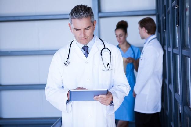 Мужской доктор смотря цифровую таблетку в больнице и коллегах стоя позади и обсуждая