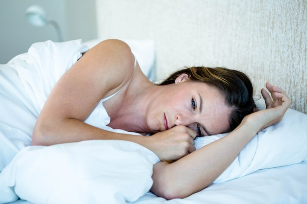 Уставшая женщина лежит в своей спальне на кровати