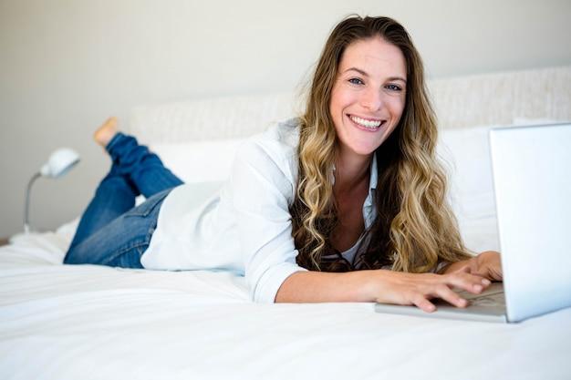 女性は彼女のラップトップで彼女のベッドに横たわって、笑みを浮かべて
