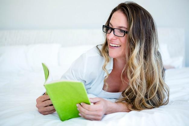 本を読んで、笑顔の彼女の上に横たわる女性