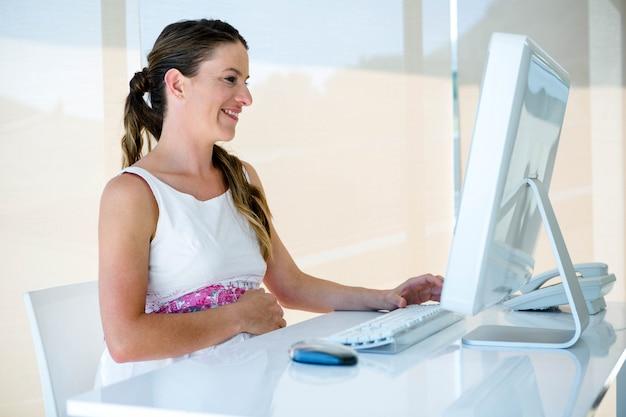 彼女の机で彼女のオフィスで笑顔の妊娠中のビジネス女性