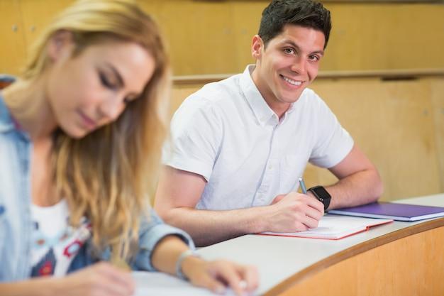 講堂でカメラに笑顔の男子生徒