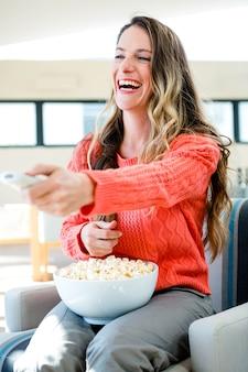 笑顔の女性、ソファに座って、ポップコーンを食べて、テレビを見て
