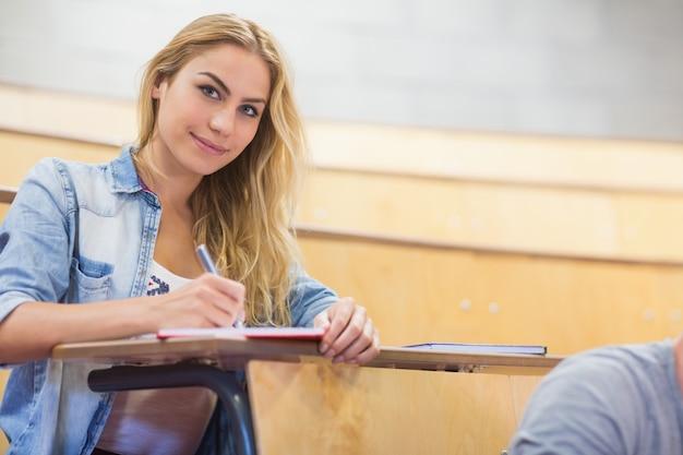 講堂での授業中に笑顔の女子学生