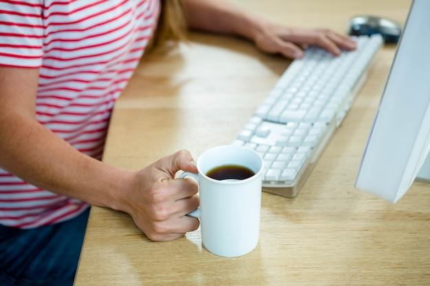 Женские руки отдыхают на столе, держа кофе и набрав
