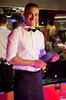 Портрет официанта, стоящего с картой меню в баре