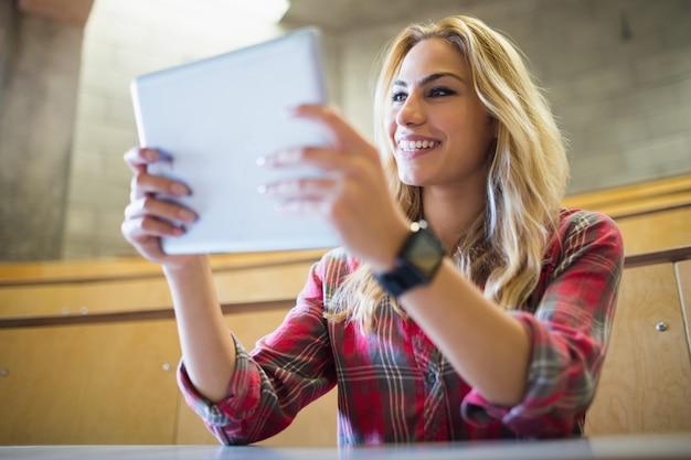 講堂でタブレットを使用して笑顔の女子学生