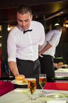 バーのテーブルでバーガーとビールを提供するウェイター