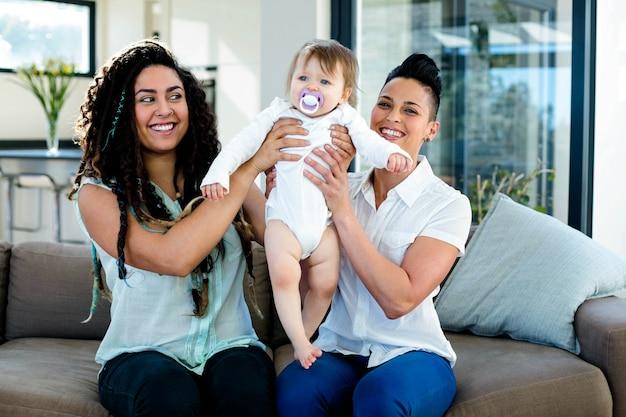 レズビアンのカップルがリビングルームで赤ちゃんと遊ぶ