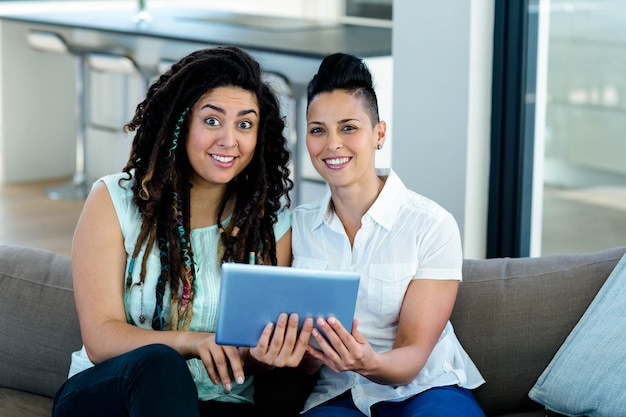 リビングルームでデジタルタブレットを使用してレズビアンのカップル
