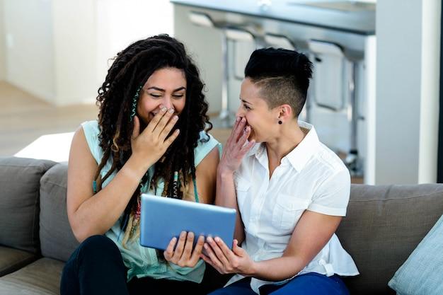 リビングルームでデジタルタブレットを使用して、笑っているレズビアンのカップル