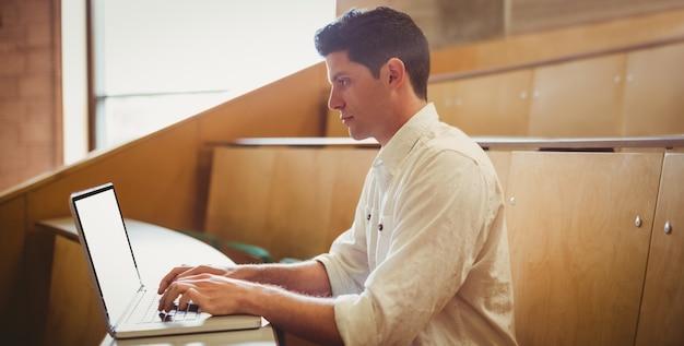 講堂でノートパソコンを使用して集中している男子生徒