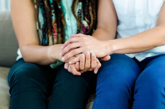 ソファの上に座って、手を繋いでいるレズビアンのカップル
