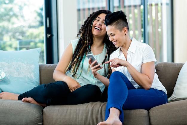 レズビアンのカップルが携帯電話を見て、リビングルームで笑顔