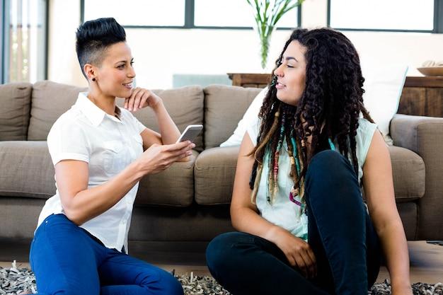 敷物の上に座って、リビングルームで携帯電話を見てレズビアンのカップルの笑顔