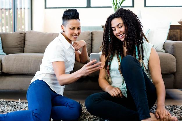 敷物の上に座って、リビングルームで携帯電話を見ているレズビアンのカップルの笑顔