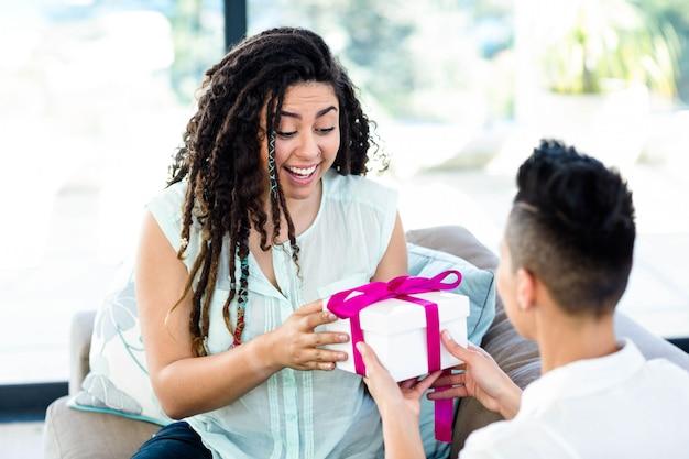 リビングルームで彼女のパートナーから贈り物を受け取る女性
