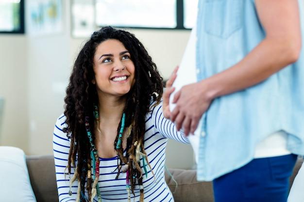妊娠中のパートナーの胃に触れながら笑顔の女性