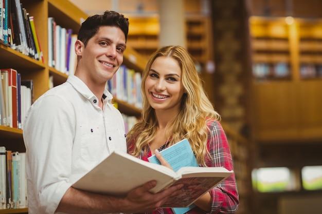 大学生が図書館で本を一緒に読んで