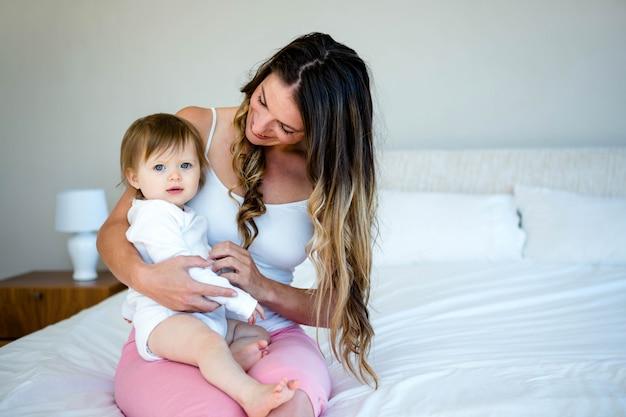 笑顔のブルネットの女性はベッドでかわいい赤ちゃんを保持しています。