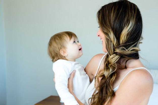 愛らしい青い目をした赤ちゃんを保持している笑顔ブルネットの女性