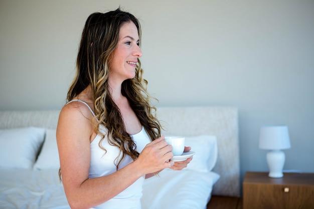 Улыбающаяся женщина сидела на кровати и держала чашку кофе
