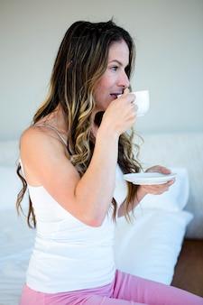 Задумчивая женщина потягивает кофе у кровати
