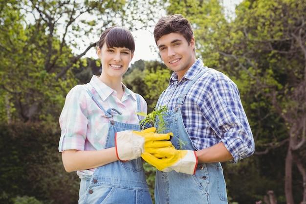 庭で苗木を保持している若いカップルの肖像画