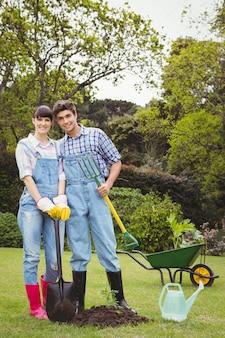 若いカップルの庭でシャベルとスペードフォークを保持