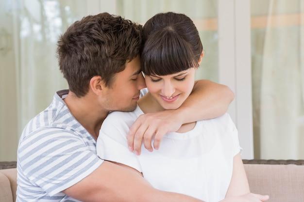 リビングルームのソファの上を受け入れるロマンチックなカップル
