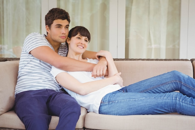 リビングルームのソファの上を受け入れる若いカップル