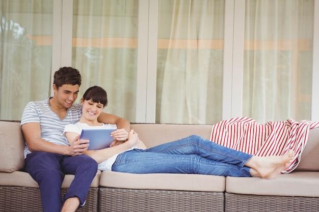 若いカップルはソファでリラックスし、リビングルームでデジタルタブレットを使用して
