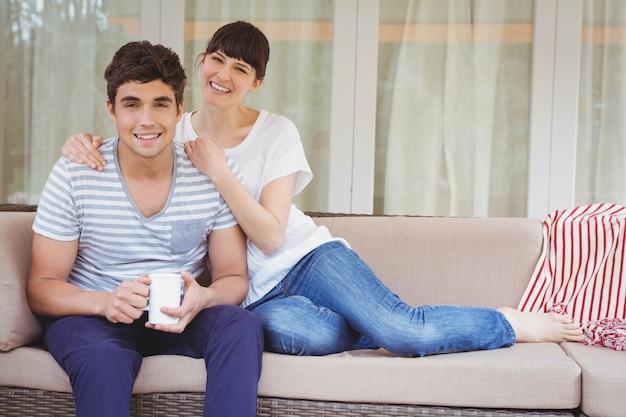 ソファに座って、リビングルームで笑顔の若いカップル