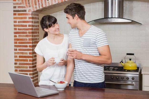 キッチンでコーヒーを飲みながら議論を持っている若いカップル