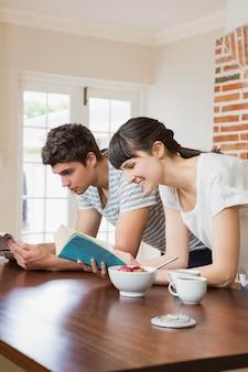 若いカップルが台所で朝食をとりながら本を読んで