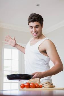 キッチンで食べ物を調理しながらフライパンを保持している若い男