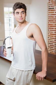 キッチンでコーヒーを飲んでいる若い男