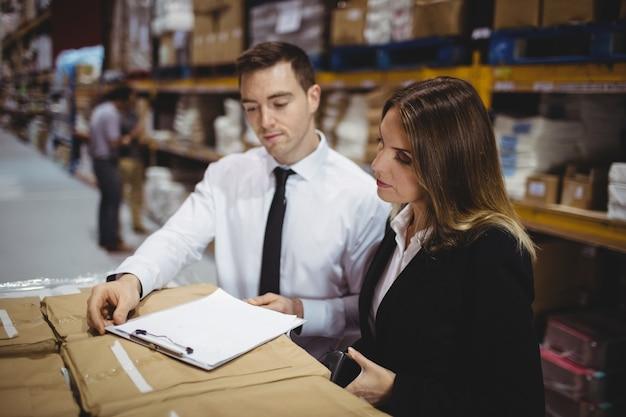 Менеджеры склада, глядя на буфер обмена на ящики