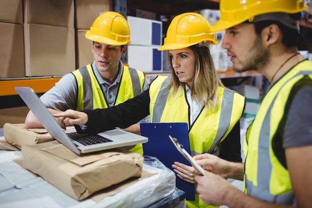 Портрет улыбающихся менеджеров склада с помощью ноутбука
