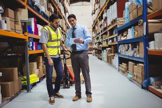 倉庫の労働者にタブレットを示すマネージャー