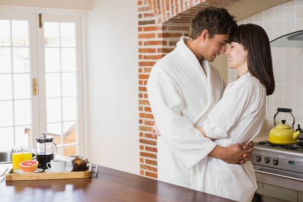 ロマンチックな若いカップルがキッチンでお互いを受け入れて