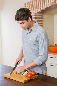 キッチンでまな板の上の若い男カット野菜