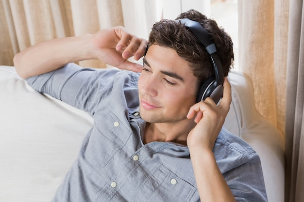 若い男が自宅で音楽を聴いてソファでリラックス